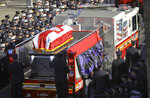Fallen firefighter Steven Pollard's casket is driven on his fire house truck through a roadway lined with thousands of firefighters, Friday Jan. 11, 2019, in New York. The 30-year-old was assigned to Ladder 170 of the Fire Department of New York when he was fatally injured last Sunday on Brooklyn's Belt Parkway. (AP Photo/Bebeto Matthews)