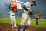 Seattle Mariners' Abraham Toro, center, has a cooler of water dumped on him by teammate Luis Torrens, left, as Toro takes part in an interview after the team's baseball game against the Houston Astros, Tuesday, Aug. 31, 2021, in Seattle. Toro hit a grand slam in the eighth inning to give the Mariners a 4-0 win. (AP Photo/Ted S. Warren)