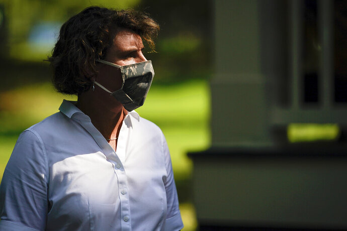 FILE - In this Aug. 25, 2020 file photo, U.S. Senate candidate Amy McGrath wears a face mask as she holds a rally with supporters during a campaign stop at Woodland Park in Lexington, Ky. Amy McGrath will face U.S. Senate Majority Leader Mitch McConnell on Election Day in November. (AP Photo/Bryan Woolston)