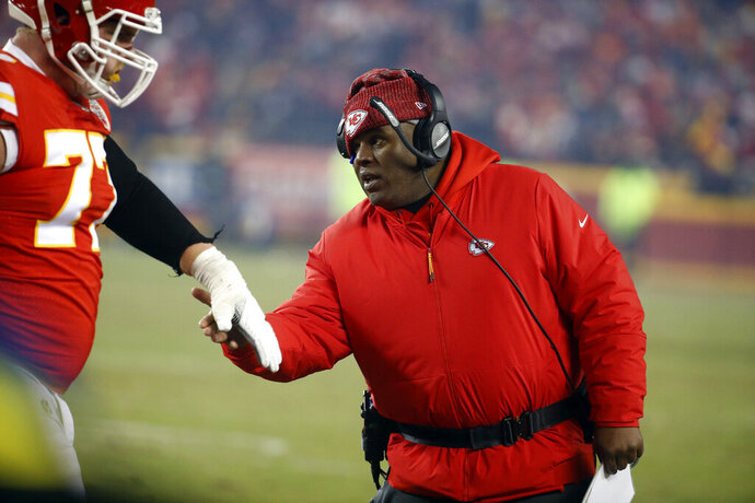 FILE - In this Jan. 20, 2019, file photo, Kansas City Chiefs offensive coordinator Eric Bieniemy greets a player during the second half of the team's AFC championship NFL football game against the New England Patriots in Kansas City, Mo. One year ago, Bieniemy and San Francisco 49ers defensive coordinator Robert Saleh missed out on the coaching carousel despite being coordinators of the two Super Bowl teams. The two figure to be near the top of many of the lists of possible head coaching candidates again this offseason when the NFL is hoping some new rules lead to more opportunities for minority coaches. (AP Photo/Charlie Riedel, File)