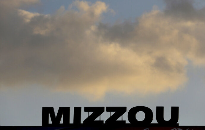 In this Nov. 2, 2013, file photo, the Mizzou logo is seen on a scoreboard over Memorial Stadium at Faurot Field before the start of an NCAA college football game between Missouri and Tennessee in Columbia, Mo. The NCAA has sanctioned Missouri's football, baseball and softball programs on Thursday, Jan. 31, 2019, after an investigation revealed academic misconduct involving a tutor who completed coursework for athletes.  (AP Photo/Jeff Roberson, File)