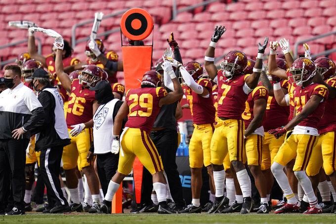 Southern California football players celebrate on the sideline  during the second half of an NCAA college football game against Arizona State, Saturday, Nov. 7, 2020, in Los Angeles. USC won 28-27. (AP Photo/Ashley Landis)