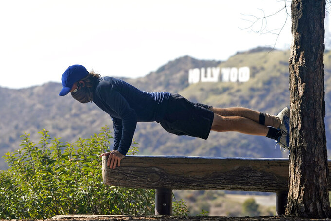 A visitor wears a mask while doing pushups on a park bench with a view of the Hollywood sign from Griffith Park amid the COVID-19 pandemic Tuesday, March 9, 2021, in Los Angeles. (AP Photo/Marcio Jose Sanchez)