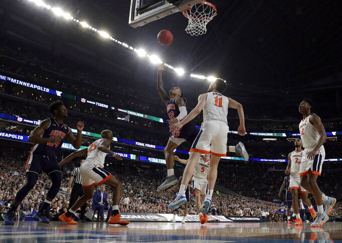 Auburn's J'Von McCormick (12) goes up for a basket against Virginia's Ty Jerome (11) during the first half in the semifinals of the Final Four NCAA college basketball tournament, Saturday, April 6, 2019, in Minneapolis. (AP Photo/David J. Phillip)