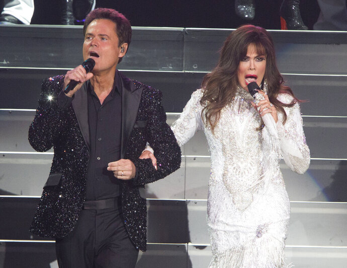 FILE - This Aug. 22, 2017 file photo shows Donny Osmond, left, and Marie Osmond performing at the Santander Arena in Reading, Pa. Donny and Marie Osmond say they will end their Las Vegas show later this year, concluding an 11-year run on the Strip. The brother-sister duo made the announcement during an appearance on