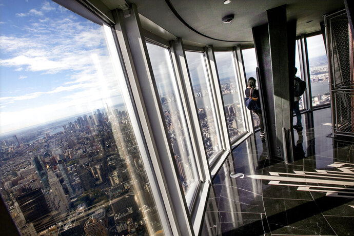 People look at the view from the 102nd floor observatory of the Empire State Building, in New York, Thursday, Oct. 10, 2019. The world-famous observatory atop the Empire State Building has a dizzying new look with floor-to-ceiling, 360-degree windows 102 floors above New York City.(AP Photo/Richard Drew)
