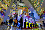 Shoppers wearing face masks to help curb the spread of the coronavirus wall by the Chinese toy maker POP Mart display booth at a shopping mall in Beijing on Dec. 9, 2020. China's economy grew 2.3% in 2020 as a recovery from the coronavirus pandemic accelerated while the United States, Europe and Japan struggled with disease flare-ups. (AP Photo/Andy Wong)