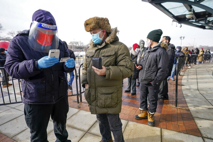 FILE - In this Wednesday, Feb. 10, 2021 photo, a health care worker, left, screens a person who waited in line at a COVID-19 vaccination site at CitiField, in the Queens borough of New York. Some New Yorkers are driving hours to get the COVID-19 vaccine because they are unable to find appointments closer to home through a state website. (AP Photo/Mary Altaffer, File)