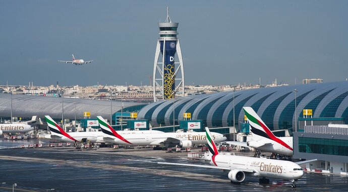 FILE - In this Dec. 11, 2019, file photo, an Emirates jetliner comes in for landing at Dubai International Airport in Dubai, United Arab Emirates. Dubai International Airport, the world's busiest for international travel, said Thursday, Jan. 23, 2020, that it is taking special precautions to screen the droves of Chinese tourists expected for the Lunar New Year holiday after the outbreak of a pneumonia-like virus that has led to China's lockdown of the entire city of Wuhan. (AP Photo/Jon Gambrell, File)