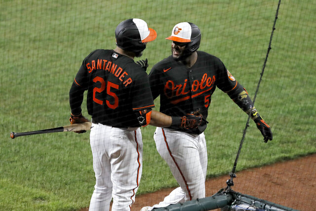 Baltimore Orioles' Hanser Alberto, right, talks with Anthony Santander (25) after hitting a solo home run off Tampa Bay Rays relief pitcher Ryan Thompson during the eighth inning of a baseball game, Friday, July 31, 2020, in Baltimore. (AP Photo/Julio Cortez)