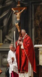 Pope Francis holds a crucifix as he celebrates Mass for the Passion of Christ, in St. Peter's Basilica, at the Vatican, Friday, April 19, 2019. Pope Francis began the Good Friday service at the Vatican with the Passion of Christ Mass and hours later will go to the ancient Colosseum in Rome for the traditional Way of the Cross procession. (AP Photo/Alessandra Tarantino)