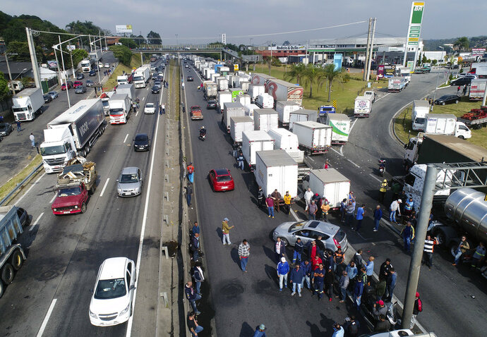 Truckers block the federal highway BR-116, which connects to Mercosur countries, to protest rising fuel costs, in Embu das Artes, on the outskirts of Sao Paulo, Brazil, Thursday, May 24, 2018. (AP Photo/Andre Penner)