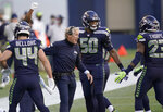 Seattle Seahawks head coach Pete Carroll celebrates with outside linebacker K.J. Wright (50) after wide receiver DK Metcalf scored a touchdown against the New England Patriots during the first half of an NFL football game, Sunday, Sept. 20, 2020, in Seattle. (AP Photo/Elaine Thompson)