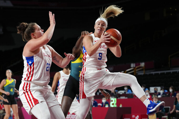 Puerto Rico's Ali Gibson (9) pulls down a rebound in front of Australia's Ezi Magbegor (13) during a women's basketball game at the 2020 Summer Olympics, Monday, Aug. 2, 2021, in Saitama, Japan. (AP Photo/Eric Gay)