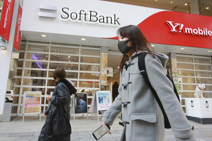 People walk by a SoftBank shop in Tokyo, Monday, Feb. 8, 2021. Japanese telecommunications and technology conglomerate Softbank Group Corp. reported Monday a whopping 1.17 trillion yen ($11 billion) profit for the October-December quarter as its investments rose in value(AP Photo/Koji Sasahara)