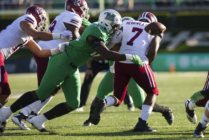 Marshall defensive lineman T.J. Johnson (15) forces Massachusetts running back Ellis Merriweather (7) to fumble on a carry during an NCAA college football game Saturday, Nov. 7, 2020, in Huntington, W.Va. (Sholten Singer/The Herald-Dispatch via AP)
