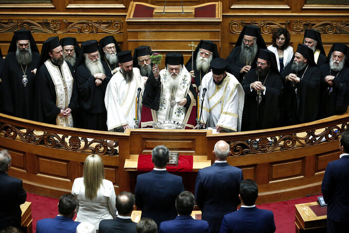 FILE - In this July 17, 2019, file photo, Greek Orthodox Archbishop Ieronymos, center, blesses lawmakers during a swearing in ceremony at the parliament in Athens. The head of the Orthodox Church of Greece, Archbishop Ieronymos, has been hospitalized after being diagnosed with COVID-19, a leading Athens hospital said Thursday, Nov. 19, 2020. (AP Photo/Yorgos Karahalis, File)