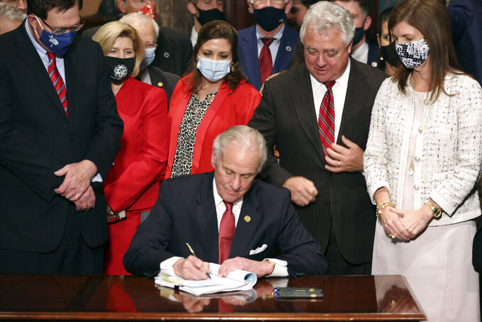 """South Carolina Gov. Henry McMaster signs into law a bill banning almost all abortions in the state Thursday, Feb. 18, 2021, in Columbia, S.C. On the same day, Planned Parenthood filed a federal lawsuit to stop the measure from going into effect.  The state House approved the """"South Carolina Fetal Heartbeat and Protection from Abortion Act"""" on a 79-35 vote Wednesday and gave it a final procedural vote Thursday before sending it to McMaster. (AP Photo/Jeffrey Collins)"""