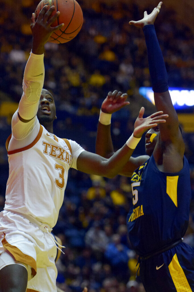 Texas guard Courtney Ramey (3) goes for a layup as West Virginia forward Lamont West (15) tries to block during the first half of an NCAA college basketball game in Morgantown, W.Va., Saturday, Feb. 9, 2019. (AP Photo/Craig Hudson)