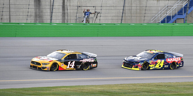 Clint Bowyer (14) is pursued by William Byron (24) during the NASCAR Cup Series auto race at Kentucky Speedway in Sparta, Ky., Saturday, July 13, 2019. (AP Photo/Timothy D. Easley)