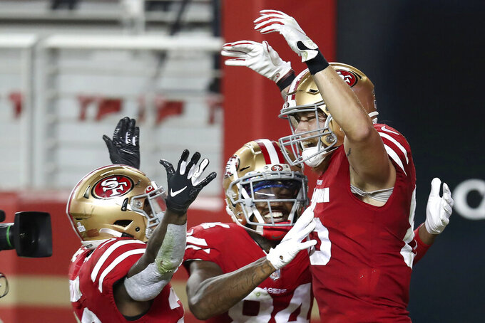 San Francisco 49ers tight end George Kittle, right, is congratulated by Jerick McKinnon, left, and Kendrick Bourne after scoring a touchdown against the Philadelphia Eagles during the second half of an NFL football game in Santa Clara, Calif., Sunday, Oct. 4, 2020. (AP Photo/Jed Jacobsohn)