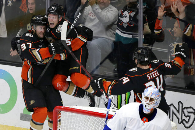 Anaheim Ducks right wing Ondrej Kase, second from left, of the Czech Republic, leaps into the arms of left wing Nick Ritchie celebrating his goal with center Sam Steel, above right, against New York Islanders goaltender Thomas Greiss, below right, of Germany, during the third period of an NHL hockey game in Anaheim, Calif., Monday, Nov. 25, 2019. (AP Photo/Alex Gallardo)