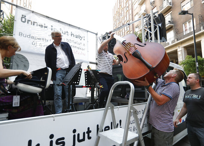 Members of the Budapest Festival Orchestra play music on the back of a truck while driving through downtown Budapest, Hungary, Wednesday June 9, 2021. The prestigious orchestra, founded and led by renowned composer Ivan Fischer, took to the streets as five members of the orchestra performed classical music to motorists and passers-by. The musical parade was aimed at encouraging Hungarians to start returning to live performances in concert halls as the pandemic wanes, after more than a year in which people were homebound and forced to take in their culture online. (AP Photo/Laszlo Balogh)