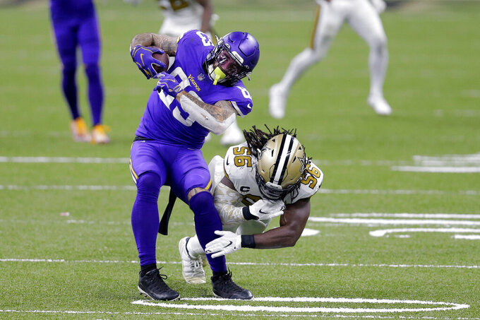 Minnesota Vikings tight end Tyler Conklin (83) pulls in a pass against New Orleans Saints outside linebacker Demario Davis (56) in the second half of an NFL football game in New Orleans, Friday, Dec. 25, 2020. (AP Photo/Brett Duke)