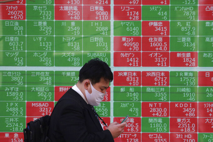 A man walks by an electronic stock board of a securities firm in Tokyo, Wednesday, March 10, 2021. Shares are higher in Asia after gains for major tech companies powered a 3.7% surge in the Nasdaq, the largest jump for the index in four months. (AP Photo/Koji Sasahara)