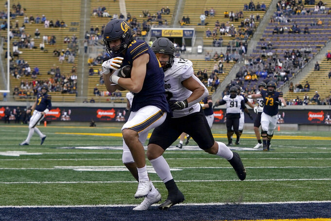 California tight end Keleki Latu, left, catches a touchdown pass against Colorado linebacker Quinn Perry during the first half of an NCAA college football game in Berkeley, Calif., Saturday, Oct. 23, 2021. (AP Photo/Jeff Chiu)