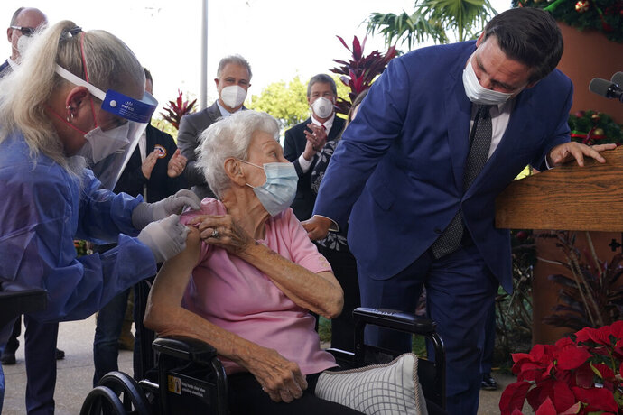 FILE - In this Dec. 16, 2020, file photo, Florida Gov. Ron DeSantis asks Vera Leip, 88, how she feels after nurse Christine Philips, left, administered the Pfizer vaccine at John Knox Village, in Pompano Beach, Fla. DeSantis is walking back his claims that his state has now vaccinated 1 million seniors. State officials acknowledged that it could take a few more days to reach the milestone. (AP Photo/Marta Lavandier, File)