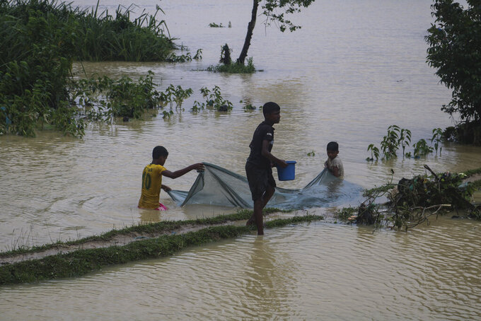Rohingya refugees fish in flood waters following heavy rains at the Rohingya refugee camp in Kutupalong, Bangladesh, Wednesday, July 28, 2021. Days of heavy rains have brought thousands of shelters in various Rohingya refugee camps in Southern Bangladesh under water, rendering thousands of refugees homeless. (AP Photo/ Shafiqur Rahman)