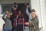 In this Dec. 6, 2019 photo, Moms 4 Housing memberDominique Walker, 34, left, activist and 2018 Oakland mayoral candidate Cat Brooks, right, and other activists react as supporters chant