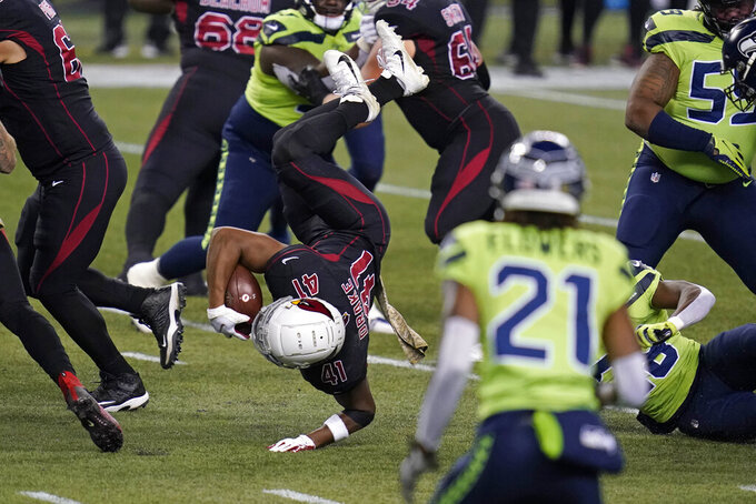 Arizona Cardinals running back Kenyan Drake (41) is upended as he rushes against the Seattle Seahawks during the first half of an NFL football game, Thursday, Nov. 19, 2020, in Seattle. (AP Photo/Elaine Thompson)