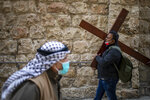 A Christian carries a cross as he walks along the Via Dolorosa towards the Church of the Holy Sepulchre, traditionally believed by many to be the site of the crucifixion of Jesus Christ, during the Good Friday procession in Jerusalem's old city, Friday, April 2, 2021. (AP Photo/Ariel Schalit)
