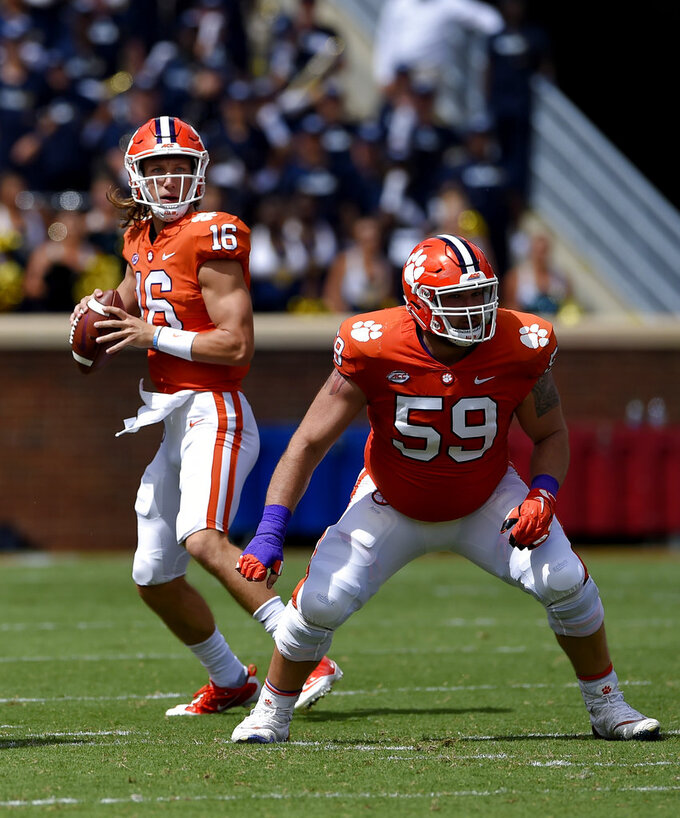 Clemson quarterback Trevor Lawrence drops back to pass with blocking help from Gage Cervenka (59) during the first half of an NCAA college football game against Georgia Southern, Saturday, Sept. 15, 2018, in Clemson, S.C. (AP Photo/Richard Shiro)
