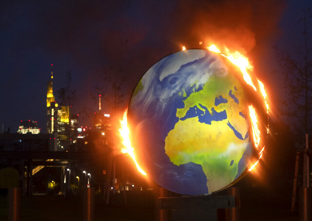 A makeshift globe burns in front of the European Central Bank in Frankfurt, Germany, Wednesday, Oct. 21, 2020. Activists of the so-called