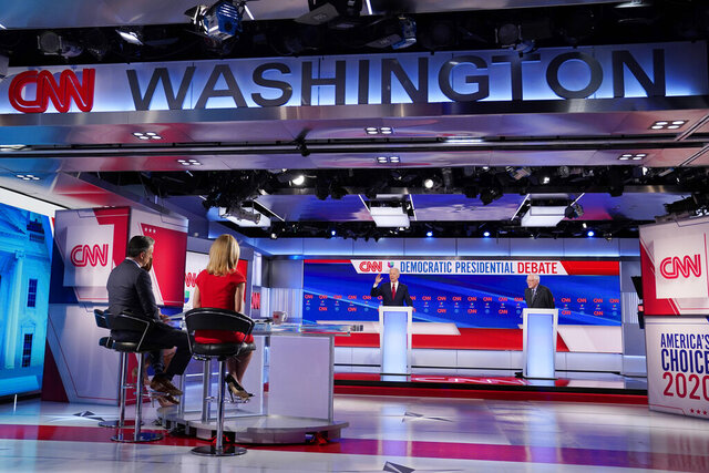 Former Vice President Joe Biden, center, and Sen. Bernie Sanders, I-Vt., far right, participate in a Democratic presidential primary debate at CNN Studios in Washington, Sunday, March 15, 2020. Looking on are from far left, Ilia Calderon, from Univision, Jake Tapper and Dana Bash, both from CNN. (AP Photo/Evan Vucci)