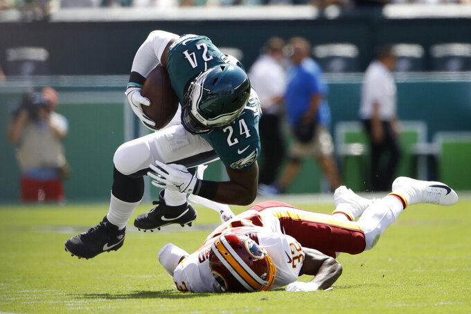 Philadelphia Eagles' Jordan Howard (24) is tackled by Washington Redskins' Jimmy Moreland (32) during the first half of an NFL football game, Sunday, Sept. 8, 2019, in Philadelphia. (AP Photo/Matt Rourke)
