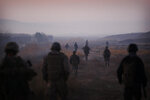 """FILE - In this Dec. 23, 2009, file photo United States Marines from the 2nd Battalion 2nd Marines """"Warlords"""" and Afghan National Army soldiers walk in formation during an operation in the Garmsir district of the volatile Helmand province, southern Afghanistan. (AP Photo/Kevin Frayer, File)"""