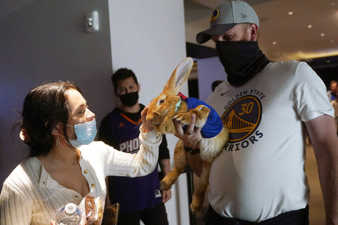 D'Ana Murillo, left, pets a therapy rabbit named Alex held by Josh Row at Chase Center before an NBA basketball game between the Golden State Warriors and the Phoenix Suns in San Francisco, Tuesday, May 11, 2021. (AP Photo/Jeff Chiu)