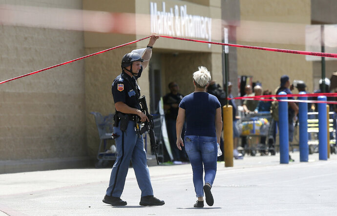 FILE - In this Aug. 3, 2019, file photo, an employee crosses into the crime scene following a shooting at a Walmart in El Paso, Texas. Walmart has quietly hired off-duty officers at dozens of its stores across El Paso, where a gunman opened fire in August at one of the retail giant's locations and killed 22 people. The move comes as Walmart plans Thursday, Nov. 14, to reopen the store where the attack happened amid ongoing lawsuits over safety. (Mark Lambie/The El Paso Times via AP, File)