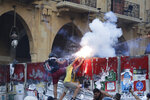 Anti-government protesters use fireworks against Lebanese riot police during a protest in the aftermath of last Tuesday's massive explosion which devastated Beirut, Lebanon, Monday, Aug. 10, 2020. (AP Photo/Hassan Ammar)
