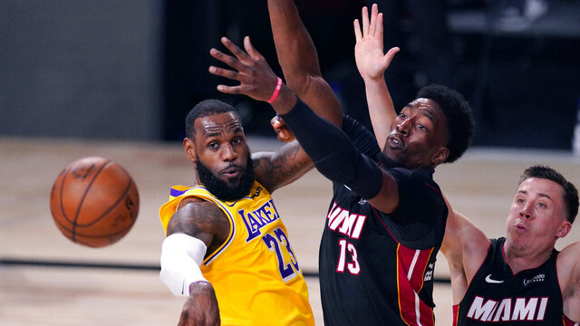 Los Angeles Lakers' LeBron James (23) passes the ball while pressured by Miami Heat's Bam Adebayo (13) during the second half of Game 1 of basketball's NBA Finals Wednesday, Sept. 30, 2020, in Lake Buena Vista, Fla. (AP Photo/Mark J. Terrill)