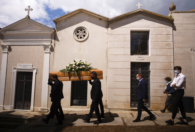 FILE - In this May 12, 2020 file photo, the casket containing the body of Annunziata Ginoble, the mother of Mayor of Roseto degli Abruzzi Sabatino Di Girolamo, third from right, with his sister, Marisa Di Felice, second from right, and his son, Francesco, right, is taken to her burial site inside the small cemetery of Montepagano, central Italy. Italy is poised to reclaim the dishonor of reporting the most coronavirus deaths in Europe, as the second surge ravages the country's disproportionately old population and exposes how public health shortfalls and delayed restrictions compounded a lack of preparedness going into the pandemic.   (AP Photo/Domenico Stinellis, file)