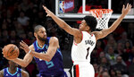 Charlotte Hornets guard Nicolas Batum, left, passes the ball around Portland Trail Blazers guard Anfernee Simons, right, during the first half of an NBA basketball game in Portland, Ore., Monday, Jan. 13, 2020. (AP Photo/Steve Dykes)