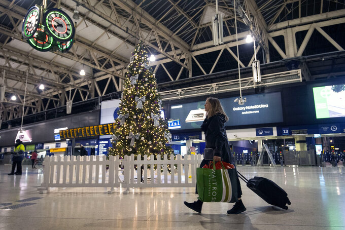 A woman pulls a suitcase past the Christmas tree on the concourse of Waterloo Station in central London, Sunday, Dec. 20, 2020. Millions of people in England have learned they must cancel their Christmas get-togethers and holiday shopping trips. British Prime Minister Boris Johnson said Saturday that holiday gatherings can't go ahead and non-essential shops must close in London and much of southern England. (Victoria Jones/PA via AP)