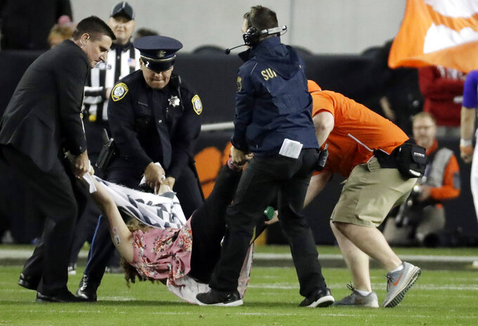 A fan is removed after running on the field during the first half the NCAA college football playoff championship game between Alabama and Clemson, Monday, Jan. 7, 2019, in Santa Clara, Calif. (AP Photo/Chris Carlson)