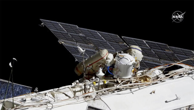 This photo provided by NASA shows Russian astronauts Commander Sergey Ryzhikov, left in red stripes, and Sergey Kud-Sverchkov on a spacewalk outside of the International Space Station on Wednesday, Nov. 18, 2020, as they prepare for next year's arrival of a long-delayed lab.  (NASA via AP)