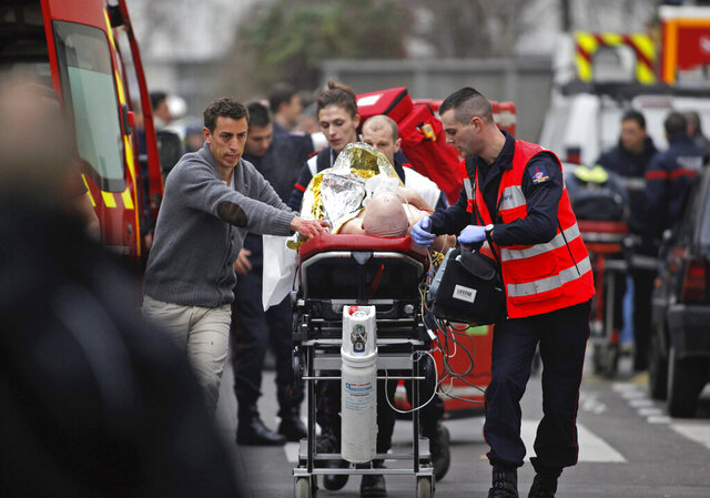 FILE - In this Jan. 7, 2015, file photo, an injured person is transported to an ambulance after a shooting at the French satirical newspaper Charlie Hebdo's office in Paris, France. The terrorism trial of 14 people linked to the January 2015 Paris attacks on the satirical weekly Charlie Hebdo and a kosher supermarket ends Wednesday after three months punctuated by new attacks, a wave of coronavirus infections among the defendants, and devastating testimony bearing witness to three days of bloodshed that shook France.(AP Photo/Thibault Camus, File)